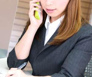 電話で相談している女性社員