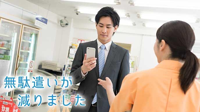 スマホアプリを見ながらコンビニで買い物を済ませる会社員