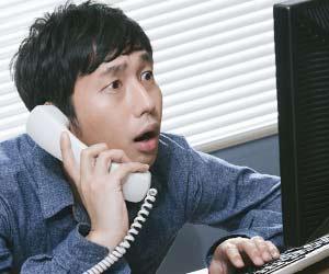 不安な顔でパソコンをのぞきこむ男性職員
