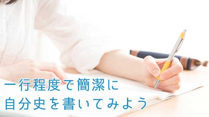 ペンを使ってノートに書いている