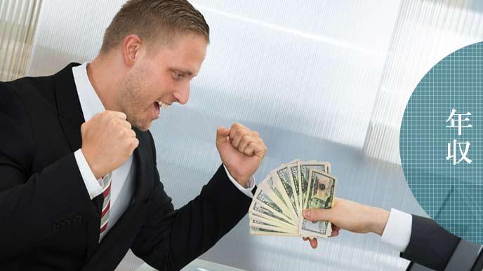 紙幣を差し出されてガッツポーズの男性