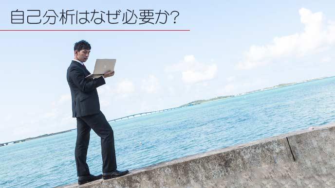海の側をノートパソコンを持って歩くビジネスマン