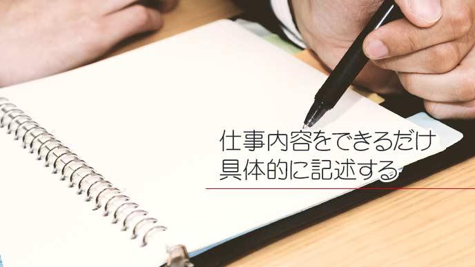手帳に文字を書き込んでいる男性サラリーマン