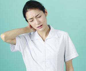 疲労して首筋に手をやる看護師