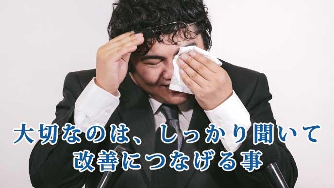 涙を拭きながら記者会見をしているビジネスマン