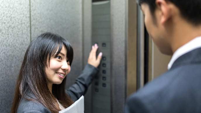エレベーターで男性社員に降りる階を聞いている女性社員