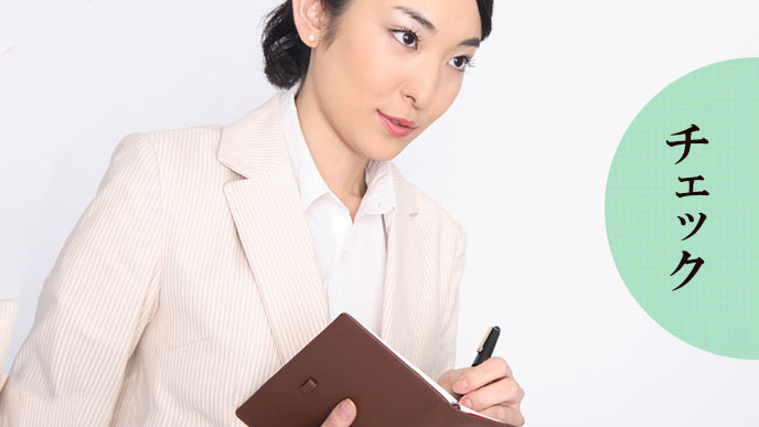 観察しながらメモ帳に書き込む女性