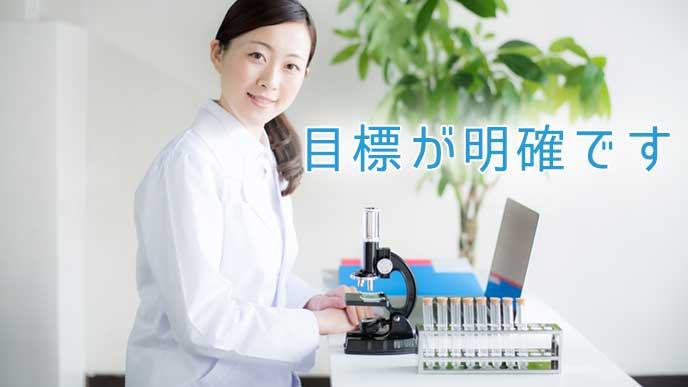 大学の研究で顕微鏡を使っている女性