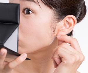 耳たぶを手鏡で確認する女性