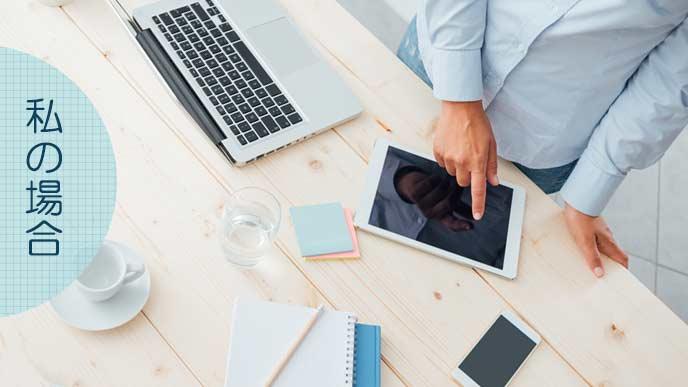 ラップトップとタブレットを机に置いて仕事