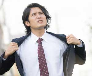 スーツを開きホットしている男性社員