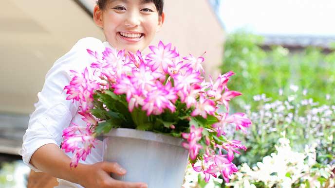 花の鉢を抱えて笑顔の女性