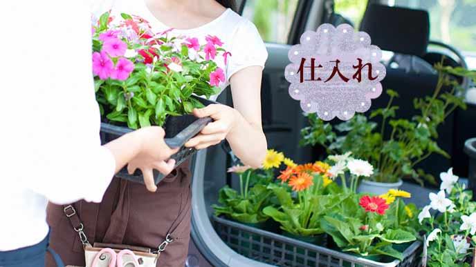 車から仕入れた花を下ろす店員