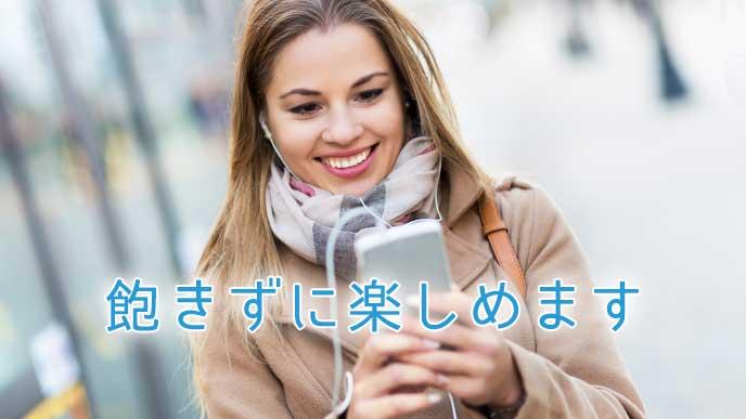バス停でスマホを見ながら嬉しそうな表情をしている女性