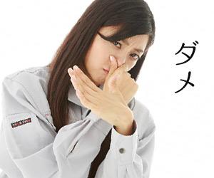 鼻をつまんでバツサインを出す女性
