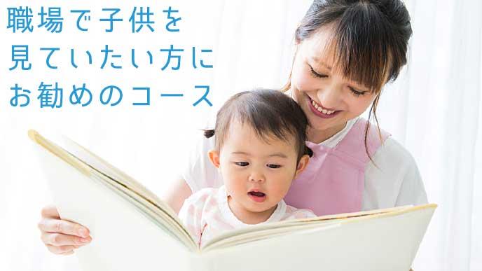 笑顔で子供に本を読ませる保育士の女性
