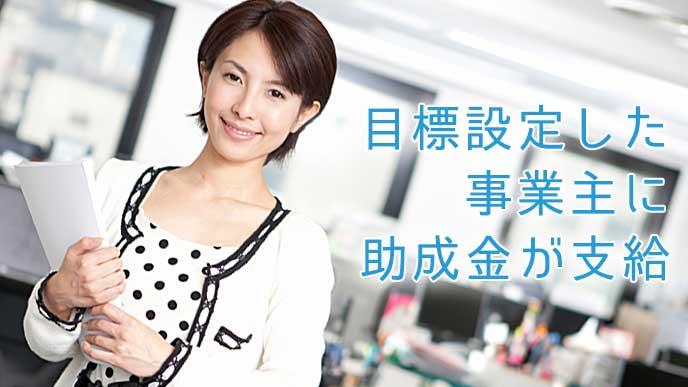 オフィスで書類を持ち微笑んでいる女性社員
