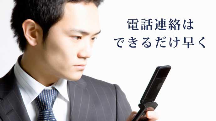 真面目な表情で携帯電話を使っているスーツ姿の男性