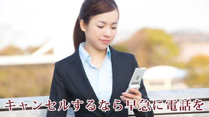 携帯電話を使っている就活生の女性