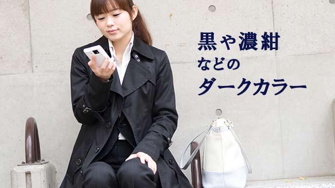 黒いコートを着てスマホを見る就活学生