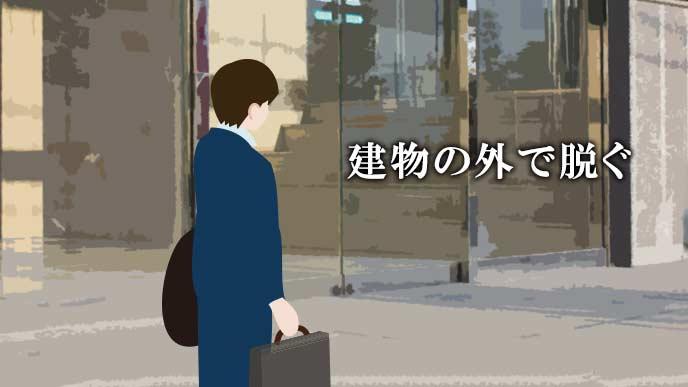 会社の玄関前でコートを脱ぐ就活学生