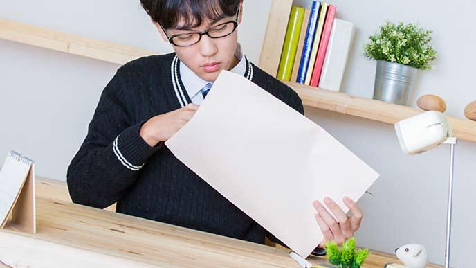 封筒に書類を入れる学生