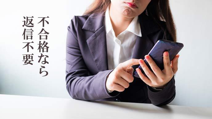 スマホでメールを読んで憮然とする女性