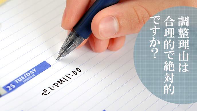 手帳に予定を書こうとする学生