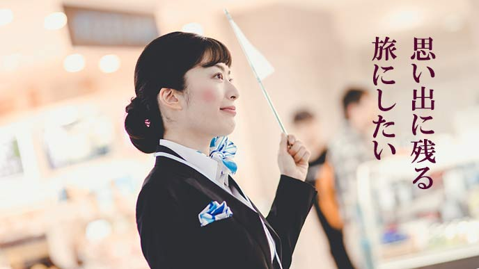 旗を持って旅行客を案内する女性