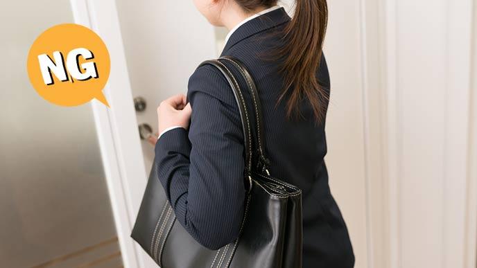 バッグを肩にかけたまま入室する就活女性