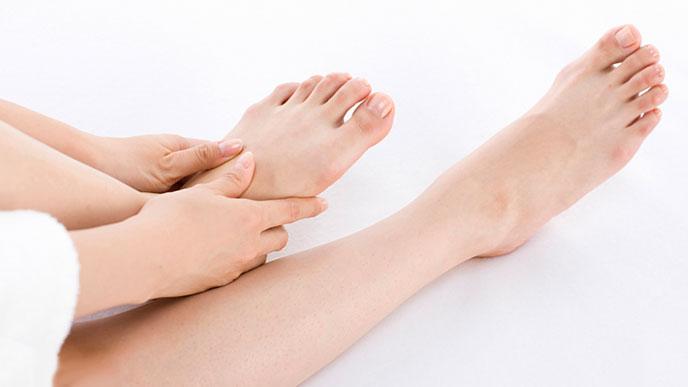 足の甲を揉む女性