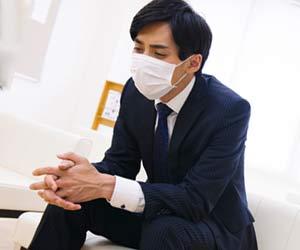 マスクをして椅子に座り込む就活学生
