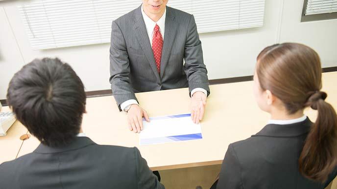企業ブースで説明を聞く就活学生