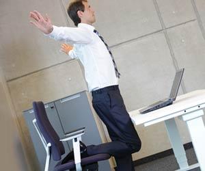 職場のデスクで片足で立つ休憩中の会社員