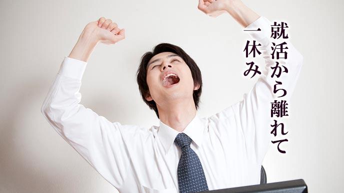 両手を上げて背伸びする就活学生