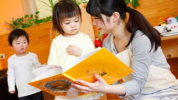 託児所で絵本を見る幼児