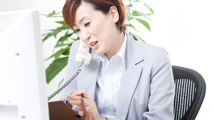 電話を受けながらメモする女性