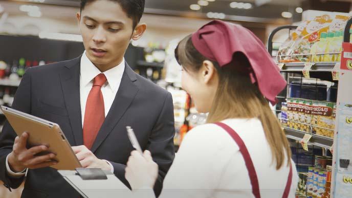 食品売り場担当者と話し合う営業マン