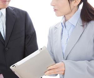 タブレットを見せながら役職者に相談する社員