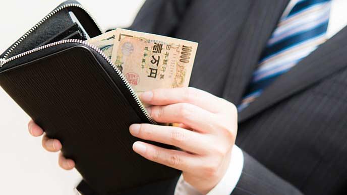 財布からお札を出す会社員