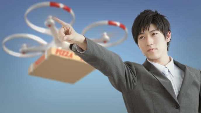 真っ直ぐに指を指して前を見据えるスーツ姿の若い男性とピザを運ぶドローン