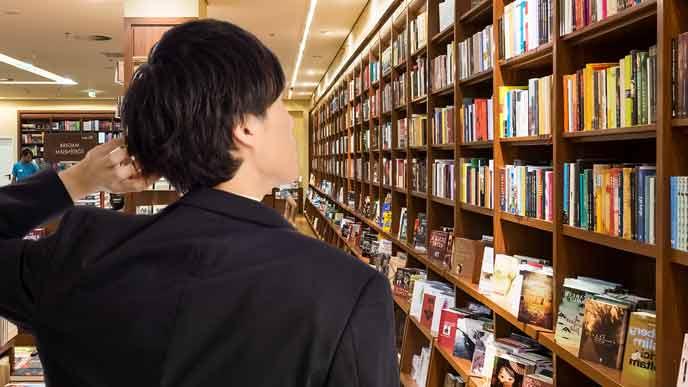 書店で本棚を探す会社員