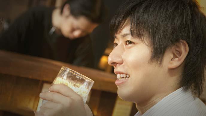 グラスを持ってぎこちなく笑う若いサラリーマン