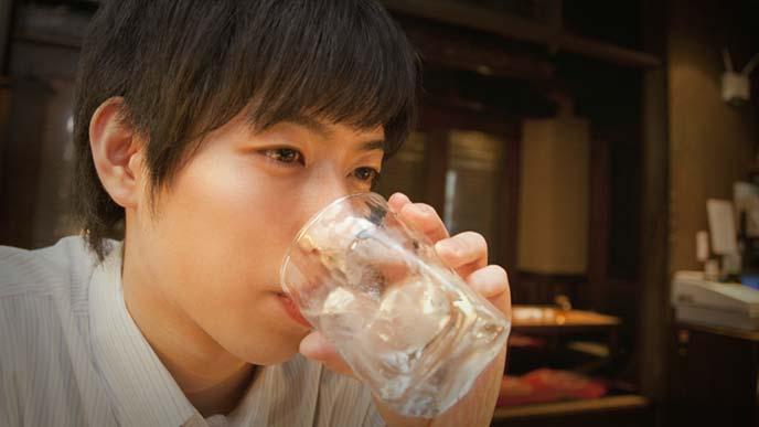 考え事をしながら一人で酒を飲む若いサラリーマン