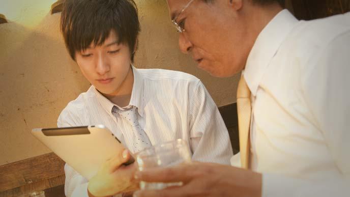 居酒屋でタブレットを操作する若いサラリーマンと、グラスを持ちながら説明を聞く上司