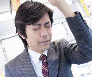 電車の吊革につかまりながら目を閉じる男性