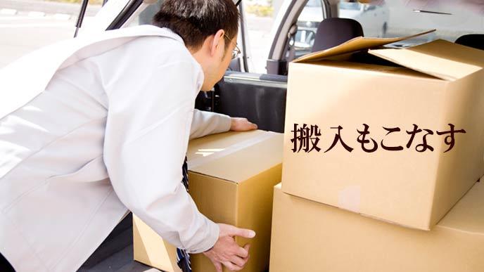 車で荷物を運ぶ営業マン