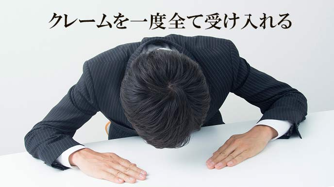机に両手をついて頭を下げる男性社員