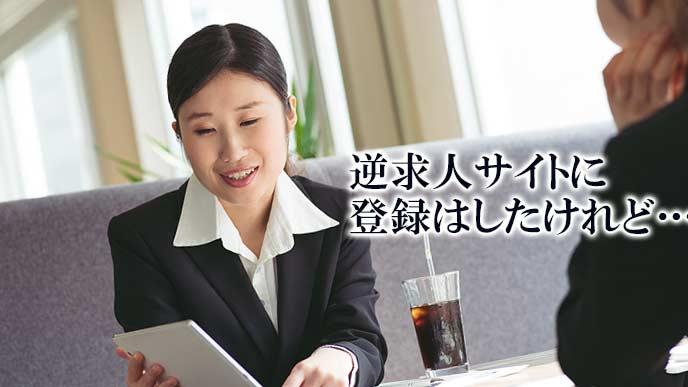 ノートパソコンを見ながら友達と話す就活学生