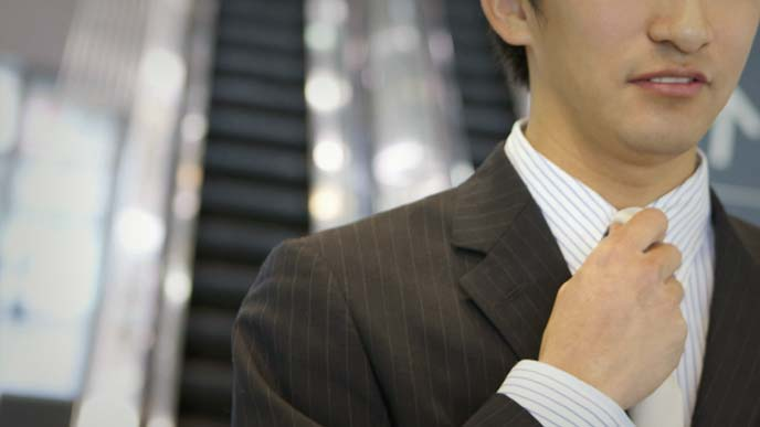エスカレータをバックにネクタイを締め直す男性